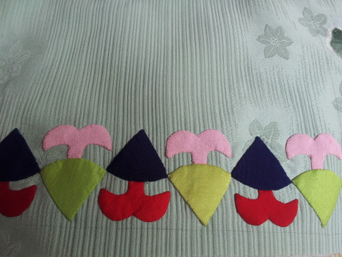 Close up of the wee Dutch Pixies you can see the texture in the back ground fabric it is heavy embossed silk.