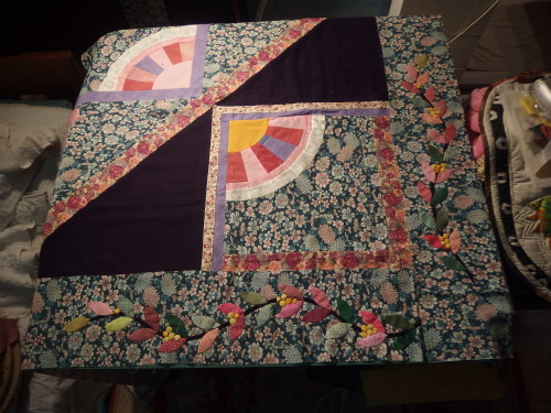 A corner of the Woollen PNG quilt with leaf borders lying beside it.