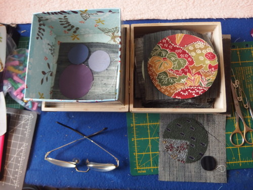 Box of circles cut out waiting to be hemed then applqiued on to the tiny squares.
