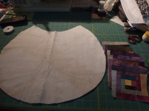 A backing shape cut out and wadding in cotton, Ive made 14,  4 inch log-cabins