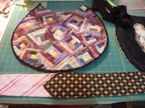 Binding sewn on and two ties waiting to be sewn together by machine.