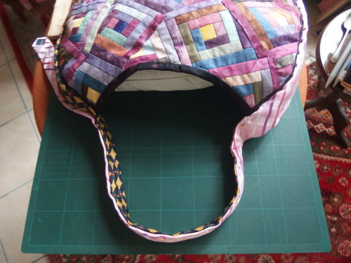 ties come up and over lap each other and form the handle for the bag, by echo quilting the ties they are more firm, stable, and don't scrunch up in the hand when carrying it.
