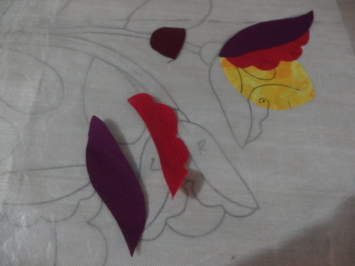 Building up the irononfusing flowers, ironing them on to a Teflon sheet which is over the pattern to guide me.