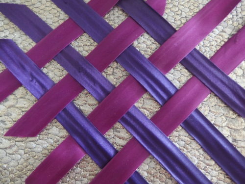I made satin bias strips then ironed on fusing strips behind them, this made it easy to weave as I ironed the tips on to the top of the basket shape and then wove the strips till i was sure they were all woven properly.